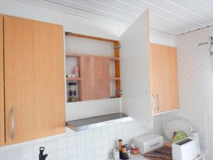 Platsbyggd kryddhylla framför köksfläkt.