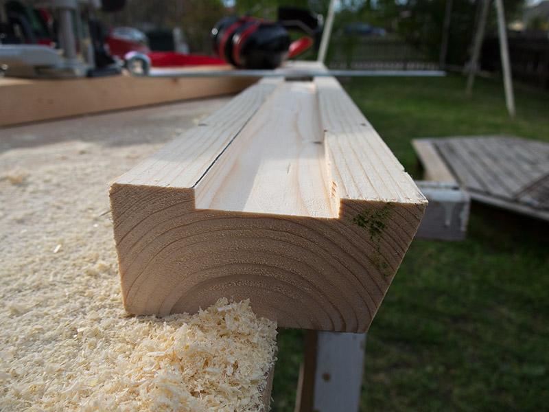 Nedsänkt spår i regel för montering av gångjärn vid bygge av soptunneskydd vid befintligt staket