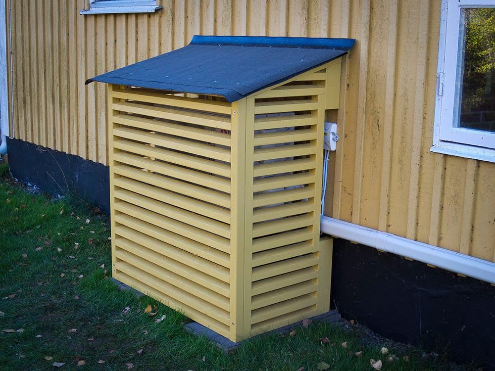 Platssnickrat skydd till luftvärmepump platsbyggd